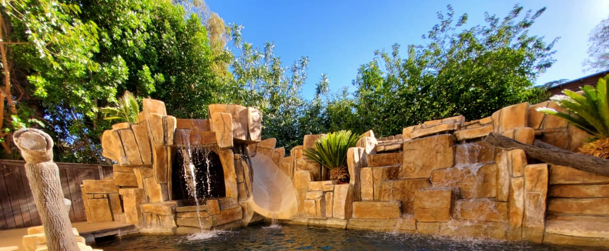 Tropical Oasis Pool with Multiple Waterfalls, Grotto, Slide and Palm Trees in Los Angeles Hero Image in Tarzana, Los Angeles, CA