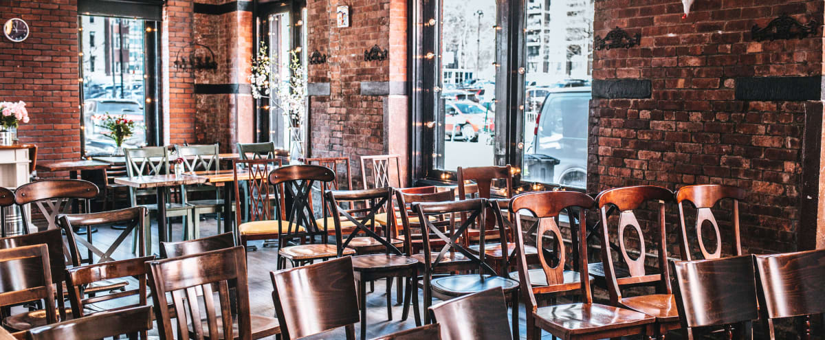 Historic landmark building, seaport, big windows, old wooden floors, simple furnishing and vintage wooden tables and chairs. in New York Hero Image in Financial District, New York, NY