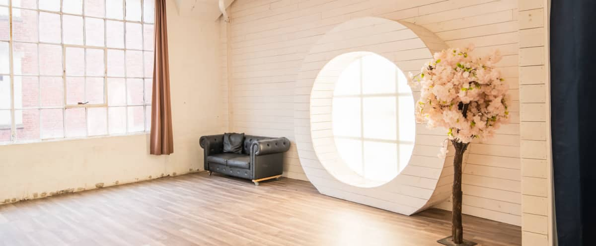 Beautiful Photo Studio with Large Round Wood Window, Laminated floor and gold wallpaper  - Studio 5 in Long Island City Hero Image in Long Island City, Long Island City, NY