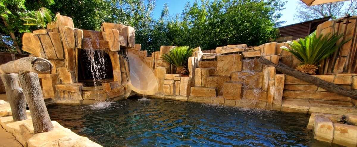 Tropical Oasis Pool with Multiple Waterfalls, Tikki's, Grotto, Slide and Palm Trees in Los Angeles Hero Image in Tarzana, Los Angeles, CA