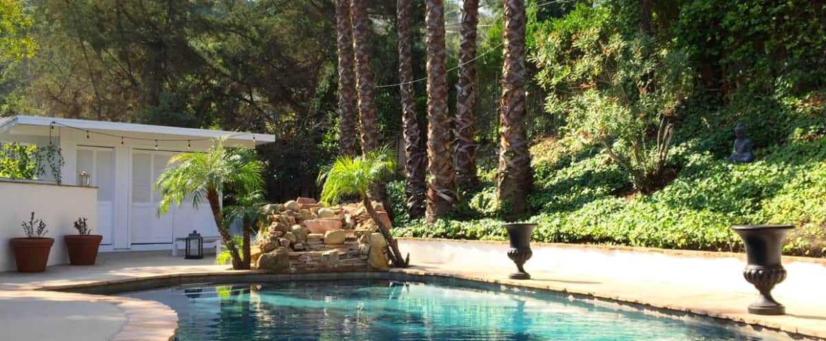Poolside Regency Glam: Cabana, Waterfall, Manicured Yard, Lava Rock Fireplace, French contemporary Kitchen & Dining. in Los Angeles Hero Image in Tarzana, Los Angeles, CA